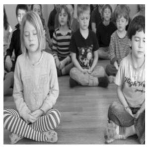 A young kids yoga class doing meditation