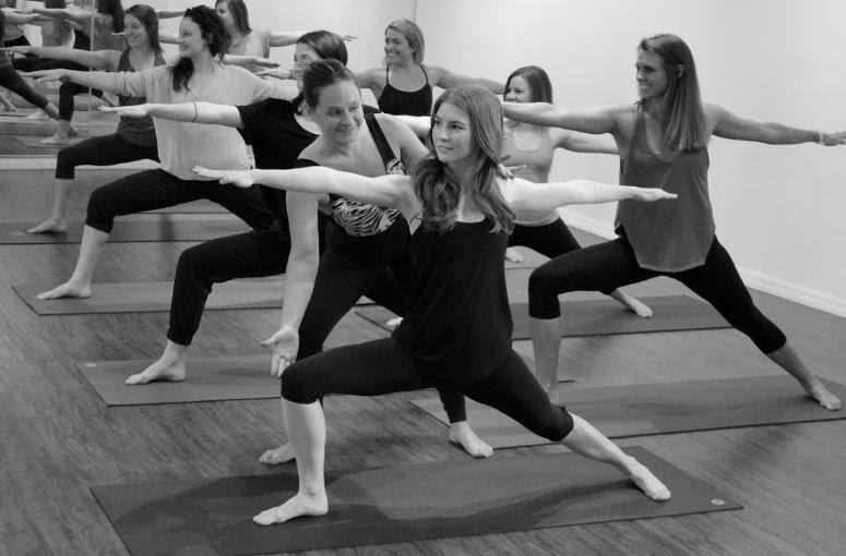A yoga teacher ajusting a student in a yoga teacher training course