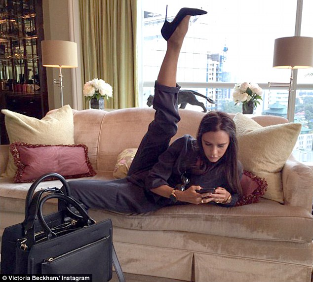 Victoria Beckham striking a yoga pose on a couch