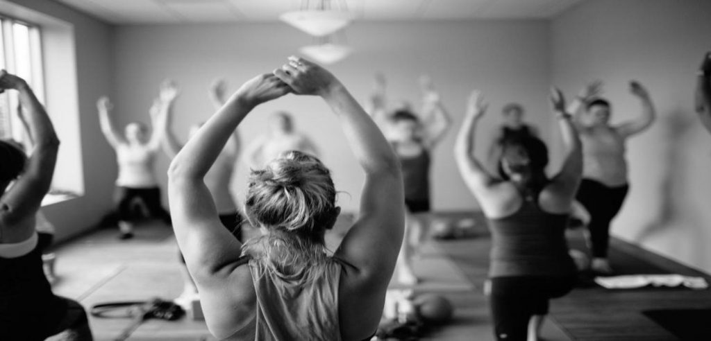 students practicing a standing pose in yoga teacher training program