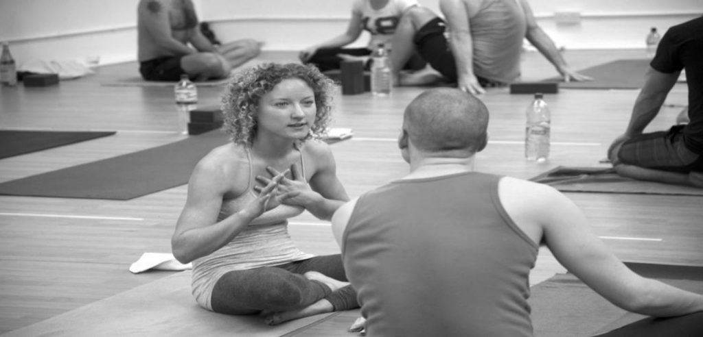 two students engaging in a yoga teacher training